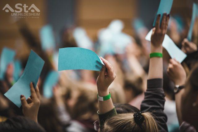 Studierende heben die Arm. Sie zeigen die blaue Stimmkarte.