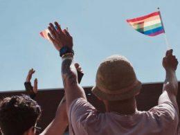 Zwei Menschen schwenken Regenbogenfahne